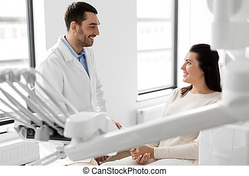 dentist talking to female patient at dental clinic