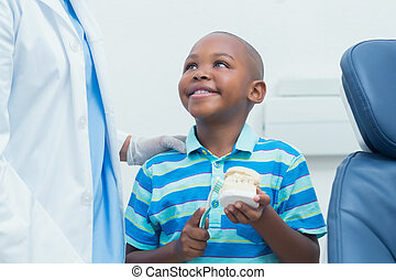 Dentist teaching boy how to brush teeth