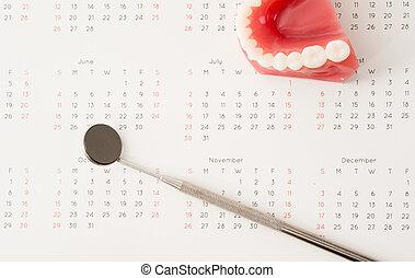 Dentist tool and demonstration teeth model on calendar