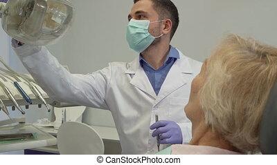Dentist turns on the dental light