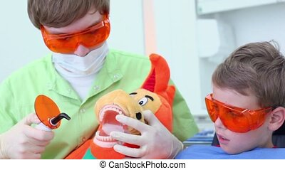 Dentist uses light for harden filling for jaw of toy near boy