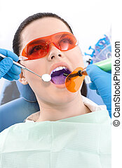 Dentist uses photopolymer lamp and dental mirror to treat teeth