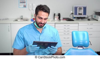 Dentist Uses Tablet - Smiling young dentist using tablet,...
