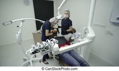 Dentist whitening teeth for patient