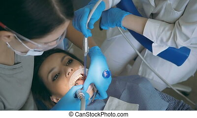 Dentist with dental nurse treating the patient teeth. Woman visiting the dental clinic, checking-up her mouth.