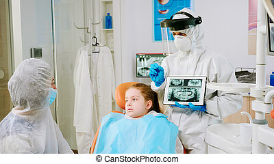 Dentist with face shield explaining panoramic mouth x-ray image to mother of kid