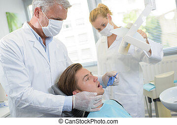 Dentist with male patient holding mouth guard