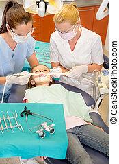 Dentist with nurse doing procedure on child