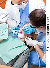 Dentist with nurse doing procedure on patient