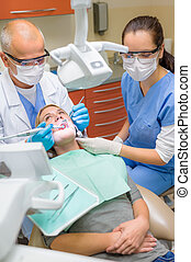 Dentist with nurse doing procedure on patient