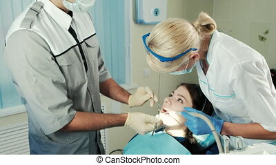 Dentist with tools inspects the jaw of the patient sitting in a chair.