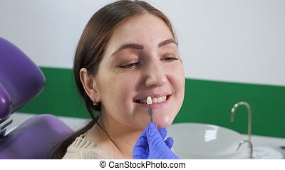 Dentist with tooth color samples is choosing shade for women patient teeth at dental clinic.