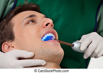 Dentist with UV Light - Patient having dental checkup with...