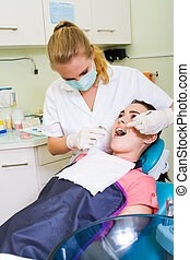dentist working - a female dentist checking her patients...