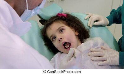 Doctor during visit of female child in dental clinic, dentist working with assistant, checking teeth of young baby girl. Sequence