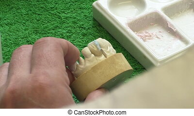 Dentist working with ceramic material, brush and dentures. Workplace dental technician. Close up