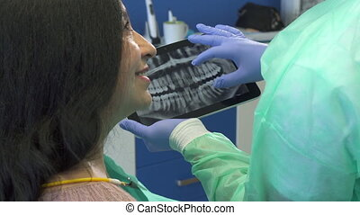 Dentist zooms x-ray image on his tablet