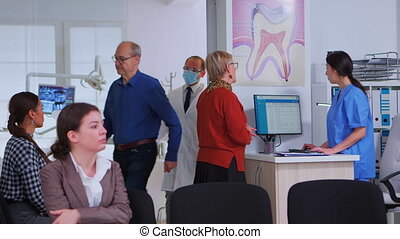 Dentistry doctor talking with senior woman standing in reception area