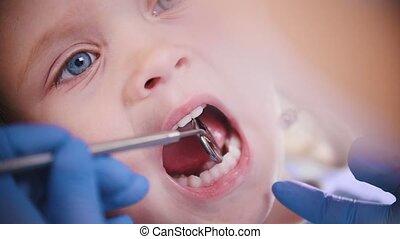 Dentistry. Female dentist examines teeth of little baby....