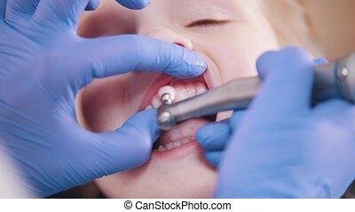 Dentistry. Female dentist polishing teeth of little baby....