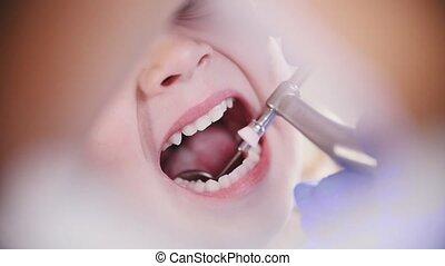 Dentistry. Female dentist polishing teeth of little baby in...