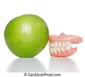 denture and apple - False teeth denture against green granny...