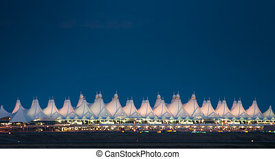 Denver International Airport at night against dark sky.