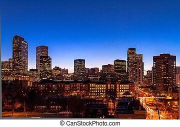 Denver Colorado skyline at dusk during the blue hour with lighted buildings and streets