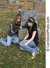 Departure - teen girls sitting in cemetary by gravestone