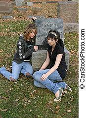teen girls sitting in cemetary by gravestone