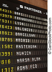 Departures - Departure schedule at an airport in Italy. ...