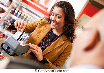 dependiente, credito, mientras, golpeando, sonriente, tarjeta
