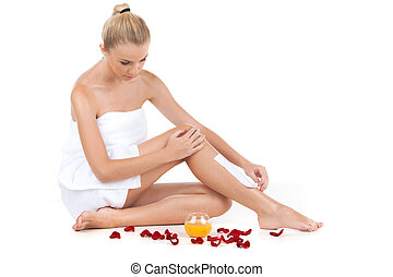depilation of female legs with waxing on white background. Young woman getting legs waxed for hair removal near scattered petals