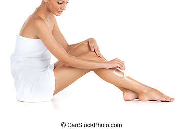 depilation of female legs with waxing on white background. Young woman getting legs waxed for hair removal