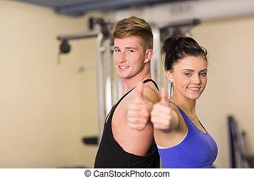 deportivo, pareja, el gesticular, pulgares arriba, en el gimnasio
