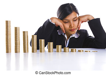 A businesswoman in background is depressed about decreasing profit month after month, showed by twelve coin stacks. Main focus on coin stacks.