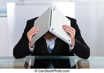 Depressed businessman hiding under his laptop - Depressed...