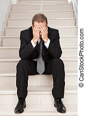 Depressed businessman. Sad mature man in formalwear covering face with hands while sitting on staircase