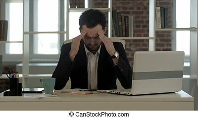 Depressed businessman sitting at computer