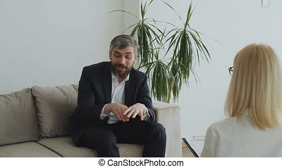 Depressed businessman talking about his porblems with female psychologist