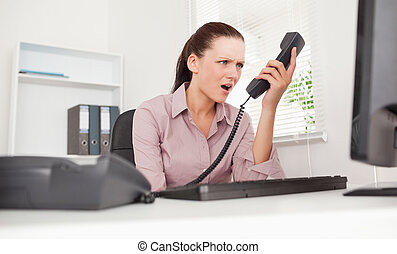 Depressed businesswoman shouting at telephone - A depressed...