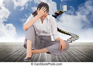 Depressed businesswoman sitting with hand on head against book steps leading to door on sky