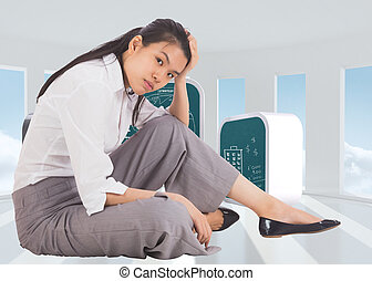 Depressed businesswoman sitting with hand on head against bright white room with windows