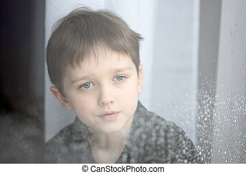 Depressed child looking out the window.