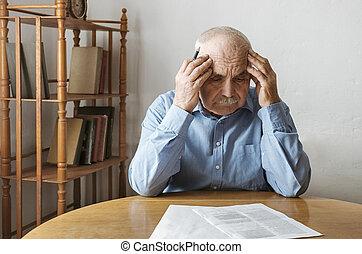Depressed, concerned senior man doing paperwork