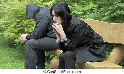 Depressed couple sitting on bench