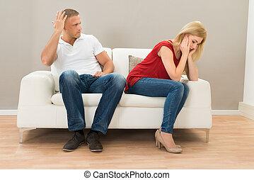 Depressed Couple Sitting On Sofa