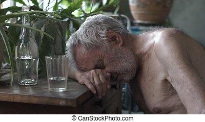 Depressed drunk man at the table - Old depressed drunk man...