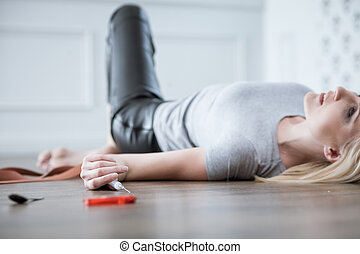 Frustrated young woman is drugging herself. She is lying on floor and holding a syringe of heroine. The woman is getting psychedelic and smiling