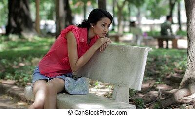 Depressed girl sitting park bench